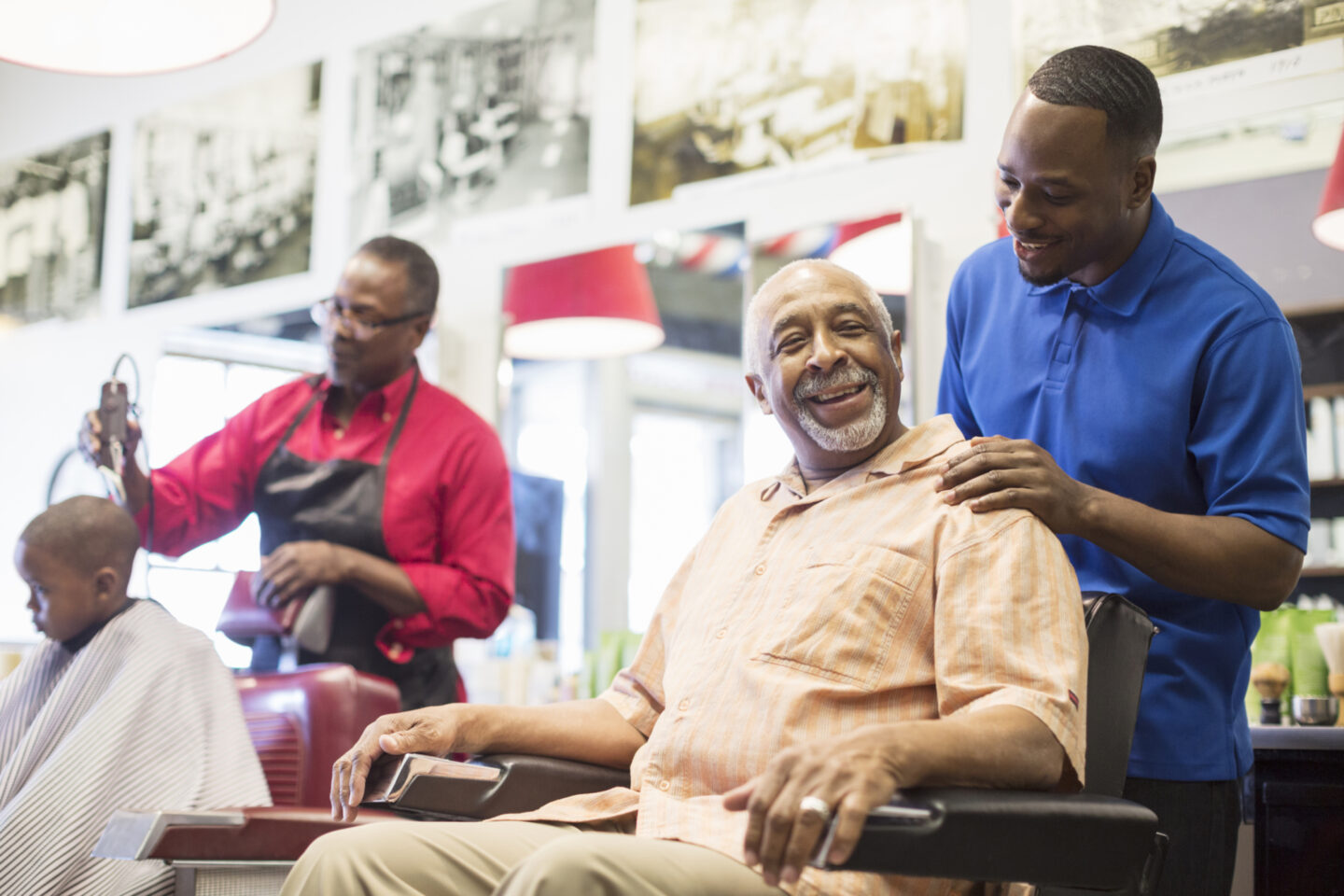 Men getting haircuts and chatting at a barber shop